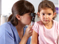 doctor looking into a little girl's ear